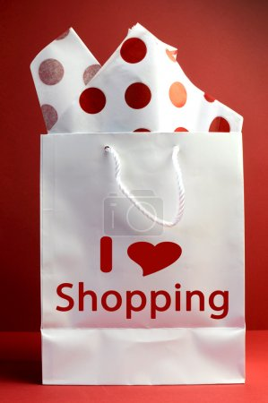Photo for I love Shopping concept with white bag and red polka dot tissue paper against a red background, vertical. - Royalty Free Image