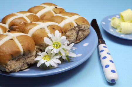 Traditional Australian and English Good Friday meal, Hot Cross Buns, on blue polka dot plate with knife and butter curls on blue background. Close-up.