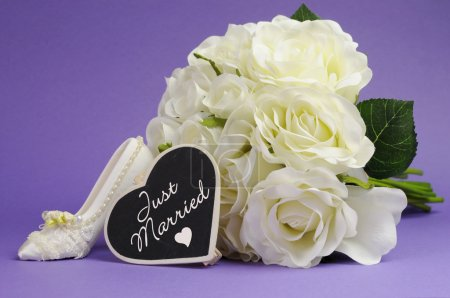 Wedding bouquet of white roses with good luck high heel shoe and heart sign with Just Married message, against purple lilac background.