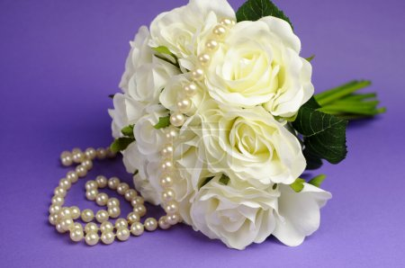 Wedding bouquet of white roses with string of pearls necklace and heart sign against purple lilac background.