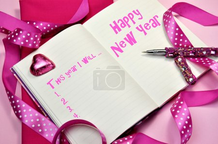 Happy New Year resolutions in diary journal book with pretty feminine pink ribbons