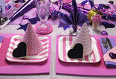 Pink and purple theme party table setting decorations.