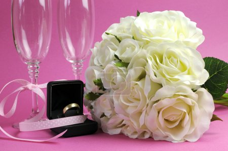 Wedding bridal bouquet of white roses on pink background with pair of champagne flute glasses and gold wedding ring in black jewelry box.
