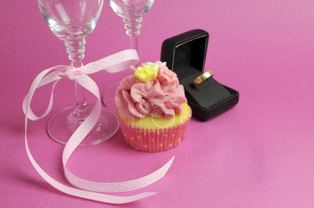 Wedding theme bridal pair of champagne flute glasses with pink cupcake and wedding ring in black jewlery box against a pink background.