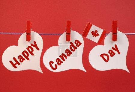 Photo pour Joyeux message de la fête du Canada avec le drapeau de la feuille d'érable canadienne accroché à des chevilles sur une ligne sur un fond rouge, pour la fête du 1er juillet . - image libre de droit