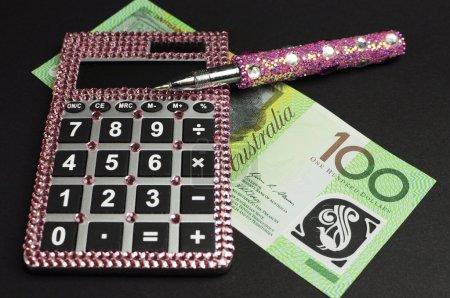 Photo pour Concept de gestion d'épargne et de l'argent avec la calculatrice de notes, rose dollar australien sur fond noir - image libre de droit