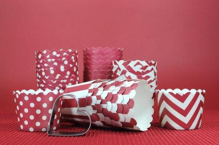 Photo pour Rouge Saint-Valentin, mariage, anniversaire ou amour thème cupcake patty pan gobelets en papier avec emporte-pièce de coeur sur fond rouge. - image libre de droit