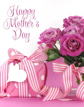 Photo for Beautiful pink gift and roses on pink and white background with sample text and copy space for your text here for Mothers Day, International Womens Day, female birthday, wedding or loving romantic present. - Royalty Free Image