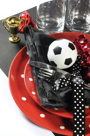 Photo pour Cadre de table de fête de football de football avec pâtés, couverts, lunettes, trophée, ballon de football et décorations en noir et blanc rouge couleurs de l'équipe - gros plan vertical . - image libre de droit