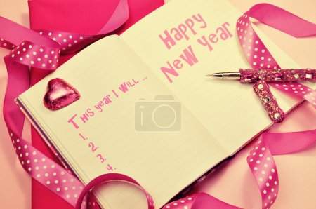 Photo for Happy New Year resolutions in diary journal book with pretty feminine pink ribbons, heart chocolate and pen with retro vintage filter. - Royalty Free Image