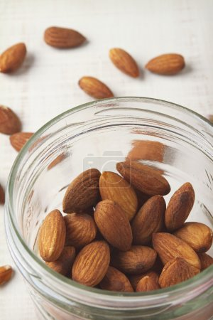 Overhead of almonds in mason jar with white rustic background