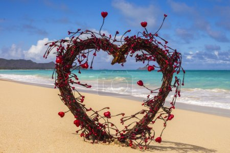 Photo for Open heart made of wood and twigs with red hearts on shore of beach - Royalty Free Image