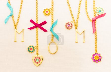 Mom spelled out in gold jewelry