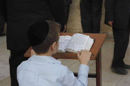 Young man reading from the Toran during Shabbat in Jerusalem, Israel