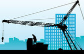 Silhouette of the building crane against a city