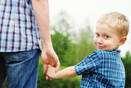 Photo pour Petit garçon tenant la main de son père - image libre de droit