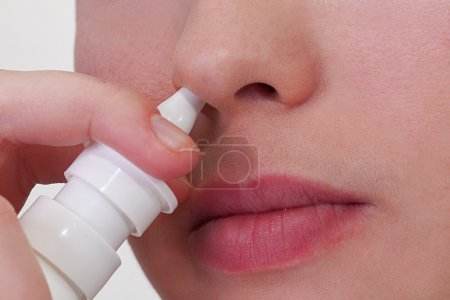 Photo for Close-up of unrecongizable woman who about to use nasal spray - Royalty Free Image