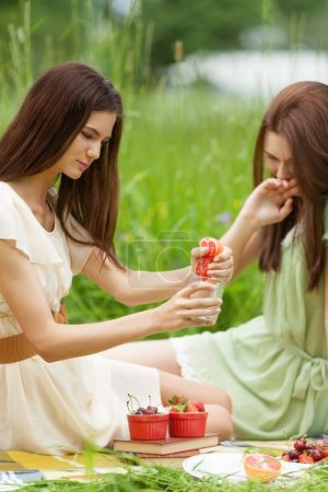 Photo for Two girl are having fun on picnic squeezing grapefruit while chasing healthy lifestyle - Royalty Free Image