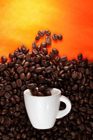 Photo for Coffee cup with beans on orange background. - Royalty Free Image