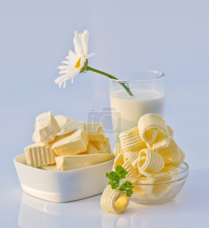 Dishes with Cut Butter, Glass of milk and Flower i...