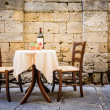Table and chairs in front of historic wall - tusca...