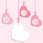 Retro fabric heart shaped tags on strings with roses in shabby chic style as Valentines day background