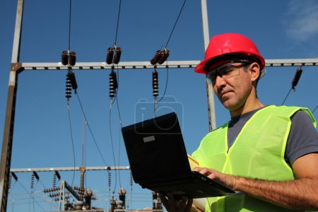 Engineer Using Laptop at an Electrical Substation.
