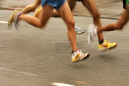 Photo for Runners legs on the road with panning blur - Royalty Free Image