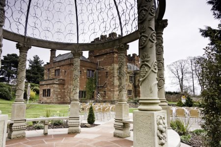 Photo for Wedding Arch at Dalston Hall. Dalston Hall is a Fifteenth Century Mansion set in the beautiful countryside on Dalston Hall, Carlisle, Cumbria, England. An exclusive wedding venue in English Lake District. Graduated filter used to prevent the sky from - Royalty Free Image
