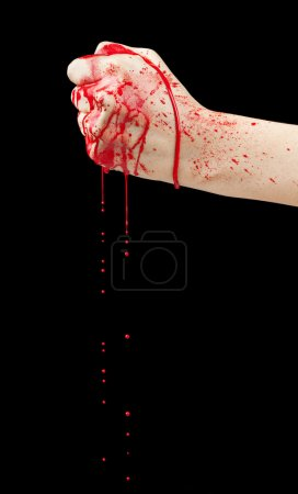 Photo for A bloody hand making a fist with blood dripping down isolated on black. - Royalty Free Image