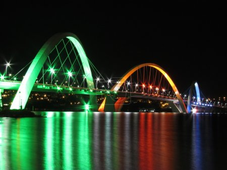 Kubitschek Bridge reflected in the lake at night with colored lighting