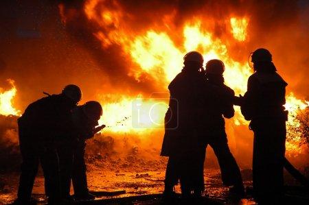 Firemen in a uniform liquidate a heavy fire....