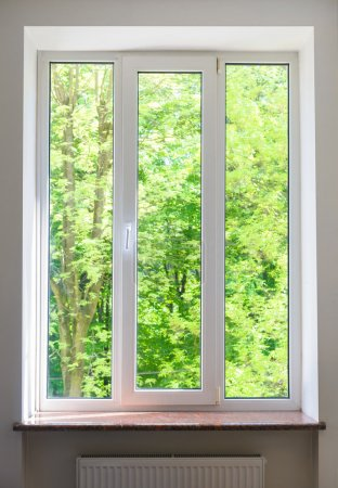 Photo for Close plastic vinyl window on a background of green trees - Royalty Free Image