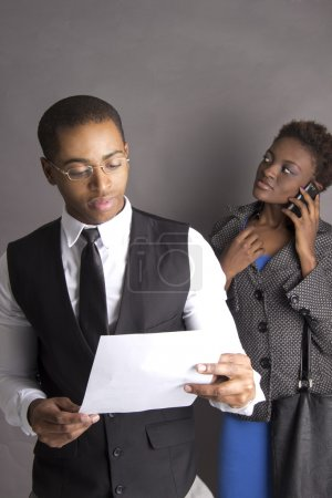 Young Business Couple busy with a contract talking on a phone