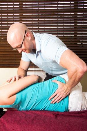 Foto de Quiropráctico masaje centrifugado menor paciente femenino joven - Imagen libre de derechos