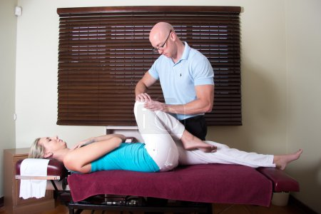 Chiropractor Strecthing Patient Leg Muscles