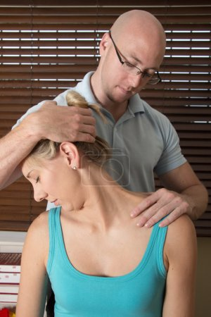 Chiropractor stretchesfemale patient neck muscles