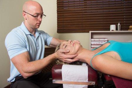 Foto de Doctore ajustando los músculos cabeza pacientes femeninos con las manos - Imagen libre de derechos