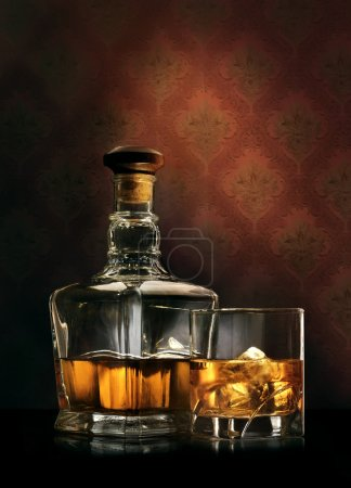 Photo for Bottle and glass of whisky with ice on wallpaper background - Royalty Free Image