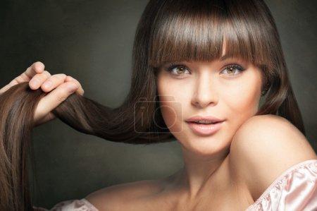 Photo pour Portrait de charmante femme brune aux cheveux longs sur fond sombre - image libre de droit