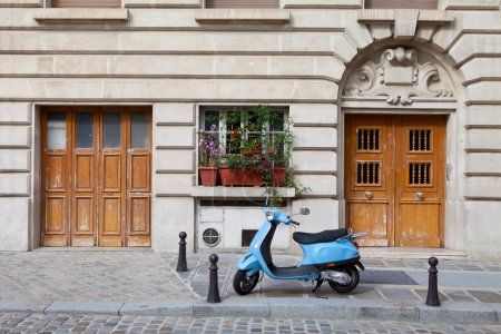 Blue retro moped parked near house on European cobblestone stree