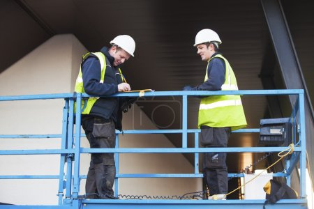 Foreman and construction worker at constraction site