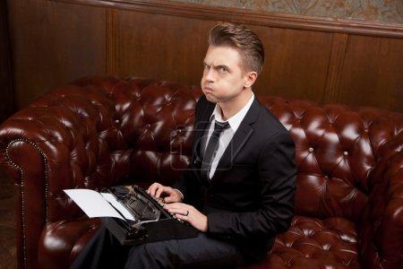 Photo pour Fou jeune homme dans un costume avec une machine à écrire - image libre de droit