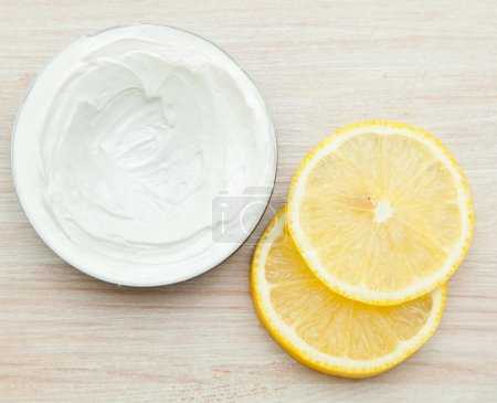 Body cream and lemon slices on the wooden table