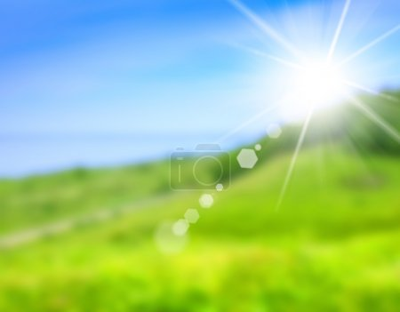 blurred picture of green field and blue sky, summer background