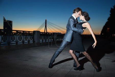Photo pour Jeune couple dansant le tango sur les quais de la ville de riga rivière, nuit - image libre de droit