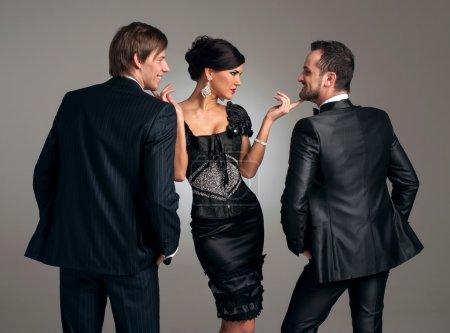 Photo for Two stylish men in suits and a girl in an evening black dress - Royalty Free Image
