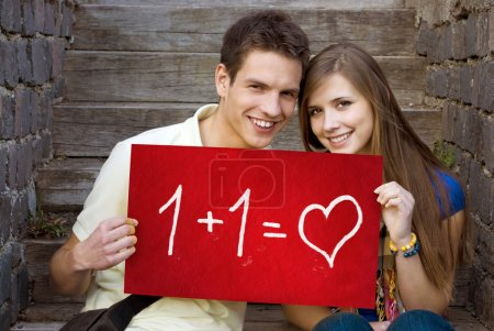 Photo for Young couple is holding board with romantic symbol. - Royalty Free Image