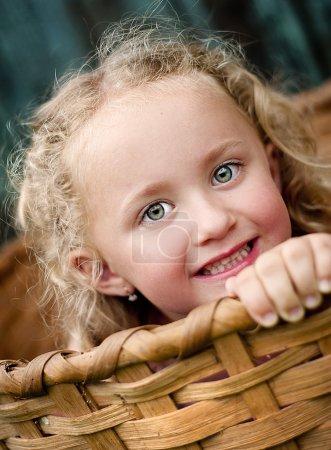 Photo pour Petite fille joue dehors et se cache dans le panier en bois - image libre de droit