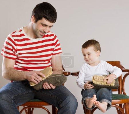 Photo pour Père et fils nettoient leurs chaussures ensemble . - image libre de droit